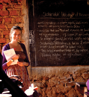 Student teacher standing in front of a chalkboard in a classroom in Uganda.