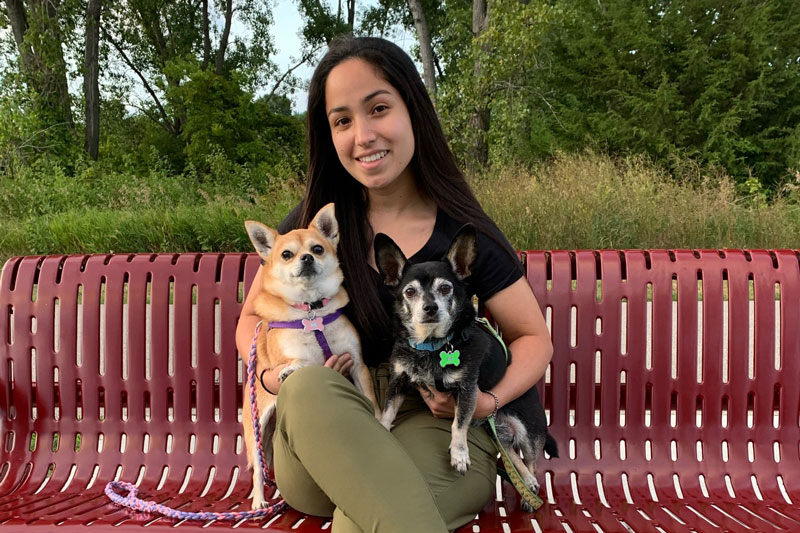 Amber Illescas sits on a bench with her two dogs.