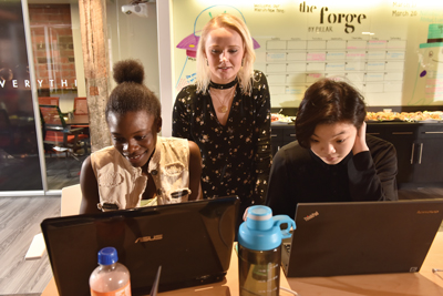 Kelsey Hrubes stands behind two girls who are sitting at a table working on computers during a coding event.