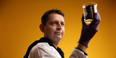 Jared Anderson holds up a beaker of coffee beans to examine them.