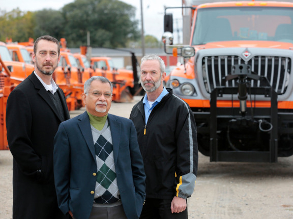 Kevin Scheibe, Sree Nilakanta and David may stand in front of the Iowa Department of Transportation's fleet of dump trucks.