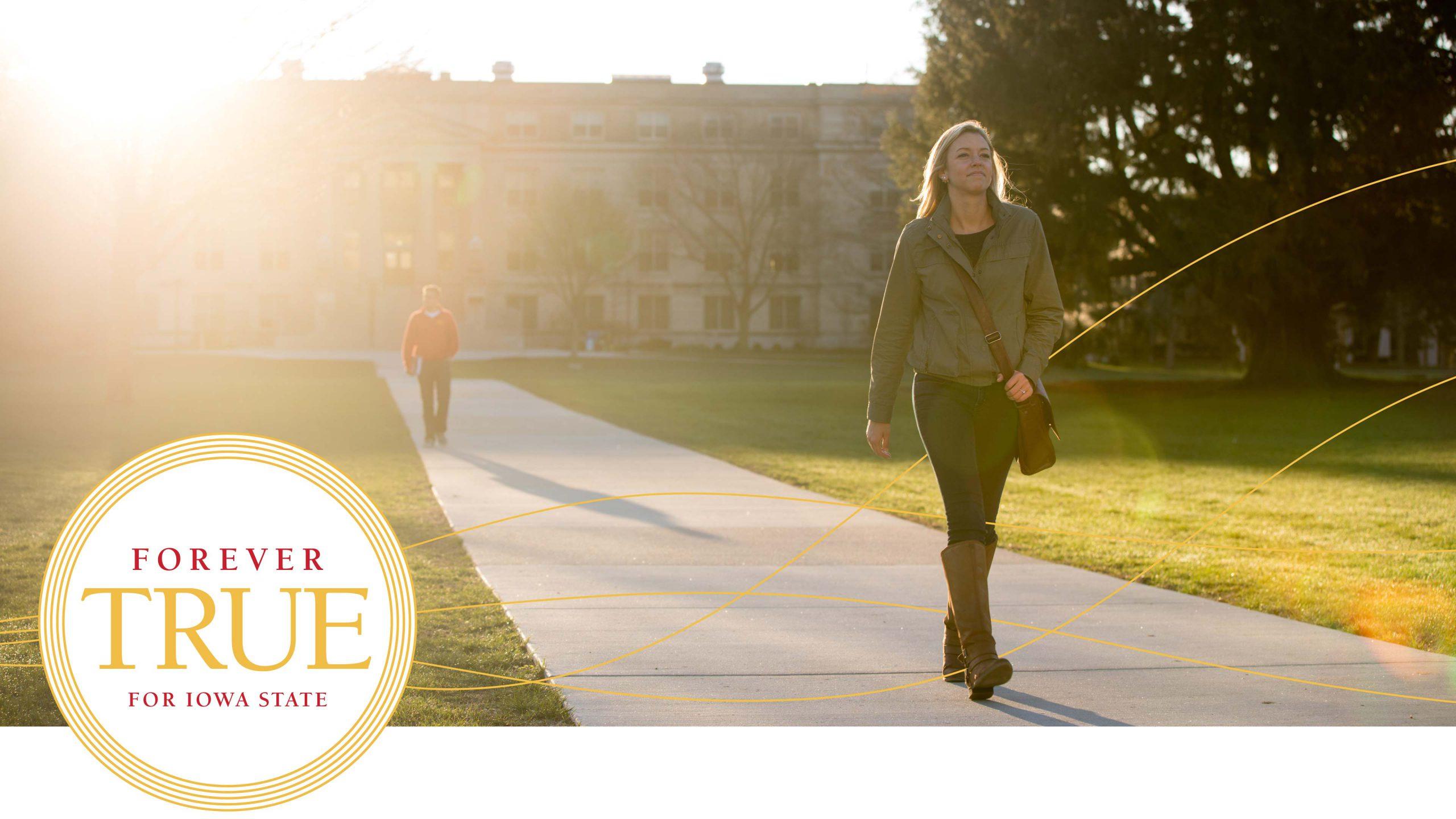 Female student walking on a sidewalk through campus.